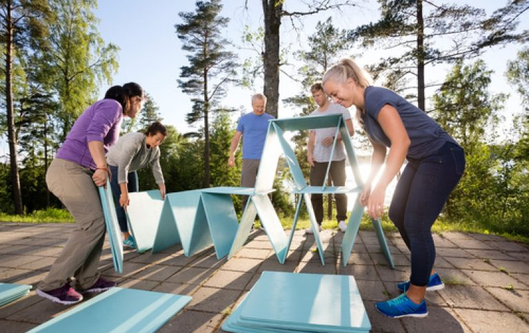 Coworkers Making Pyramid With Blue Planks On Patio